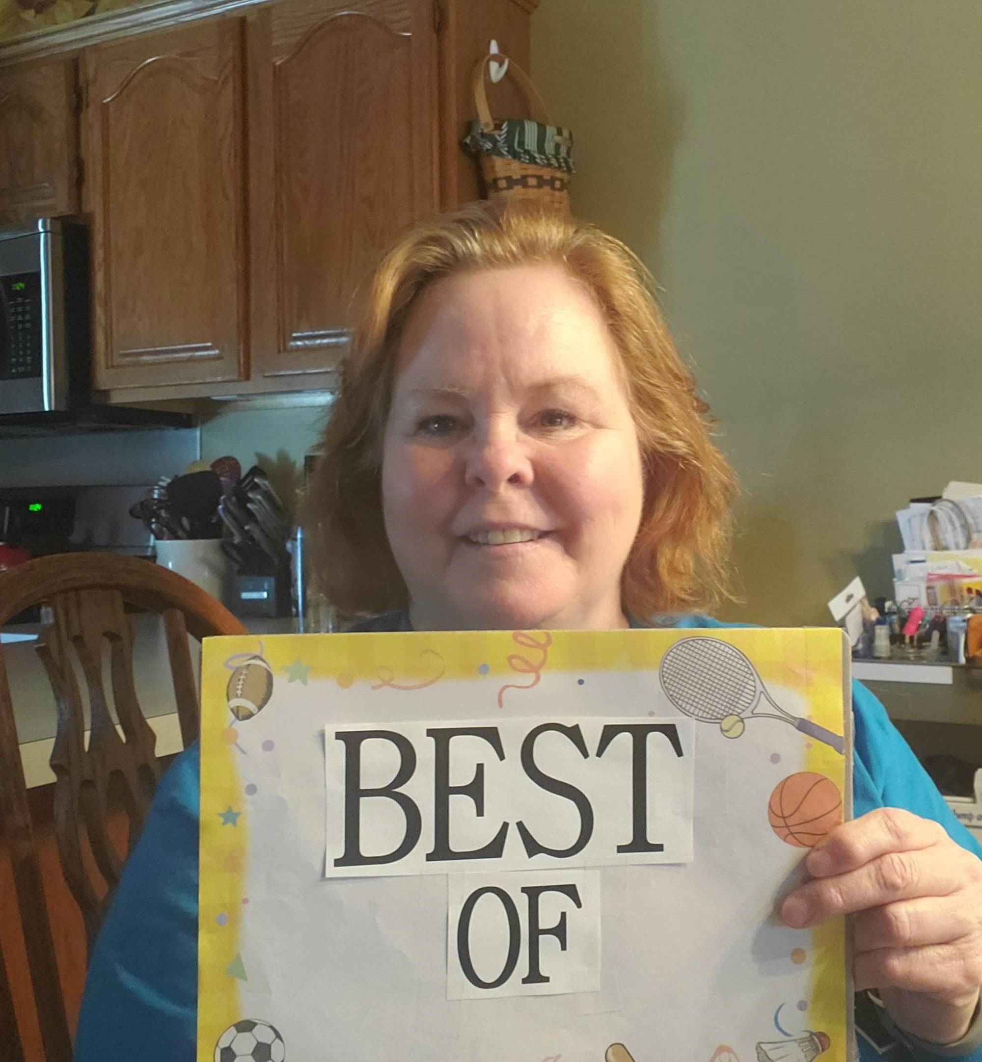 "Faculty holding sign that reads ""best of"""